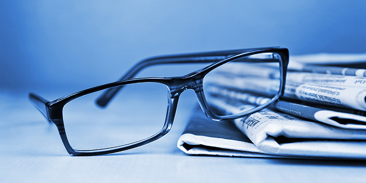 eyeglasses and newspaper blue background
